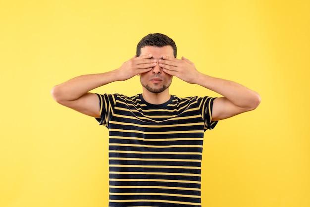 Schöner mann der vorderansicht im schwarz-weiß gestreiften t-shirt, das augen mit händen auf gelbem lokalisiertem hintergrund bedeckt