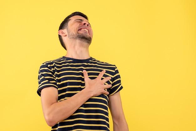 Schöner mann der vorderansicht im schwarz-weiß gestreiften t-shirt, das brust mit schmerz auf gelbem lokalisiertem hintergrund hält