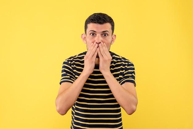 Schöner mann der vorderansicht im schwarz-weiß gestreiften t-shirt, das hände auf gesicht auf gelbem lokalisiertem hintergrund setzt