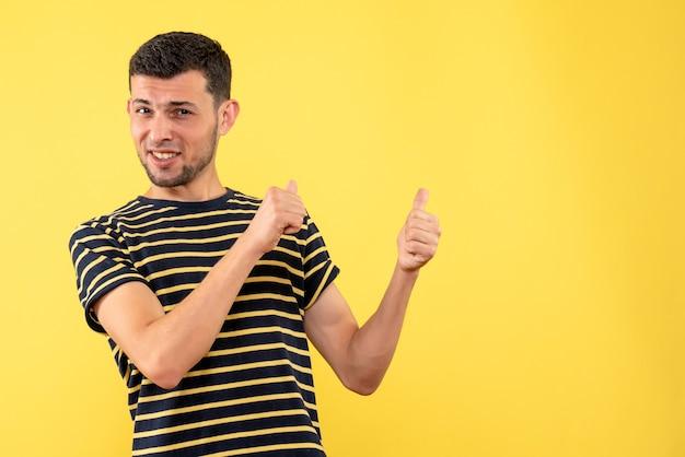 Schöner mann der vorderansicht im schwarz-weiß gestreiften t-shirt, das hinten auf gelbem lokalisiertem hintergrund zeigt
