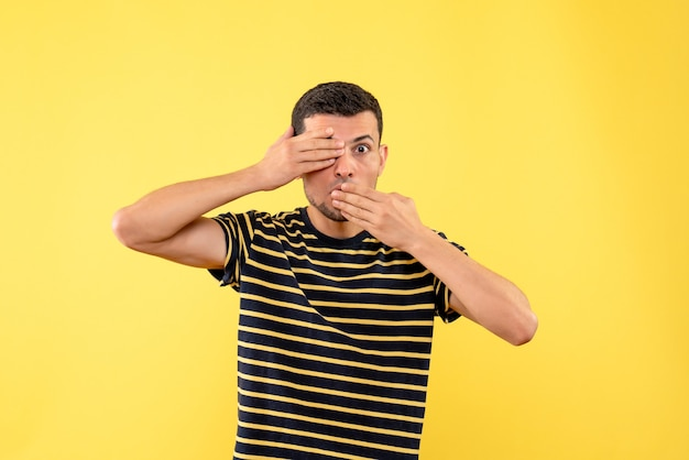 Schöner mann der vorderansicht im schwarz-weiß gestreiften t-shirt, das mund und augen auf gelbem lokalisiertem hintergrund bedeckt