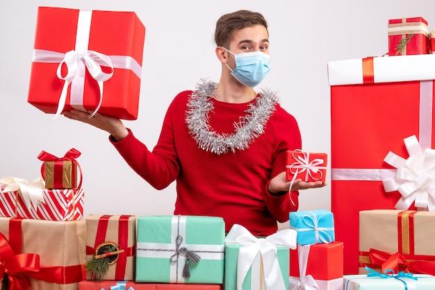 Schöner mann der vorderansicht mit maske, die um weihnachtsgeschenke sitzt
