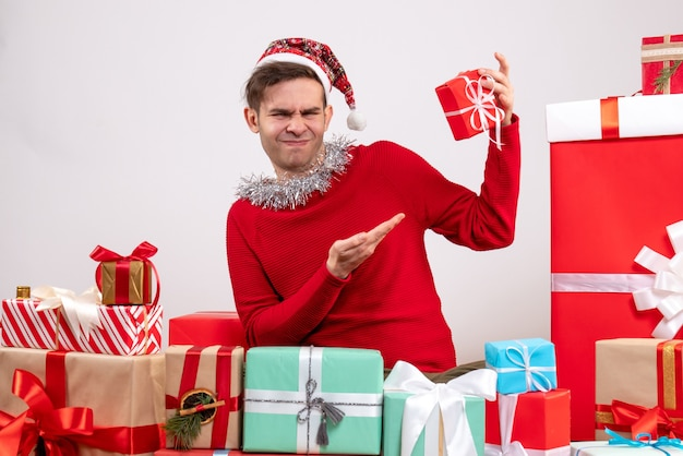 Schöner mann der vorderansicht mit snata-hut, der um weihnachtsgeschenke sitzt