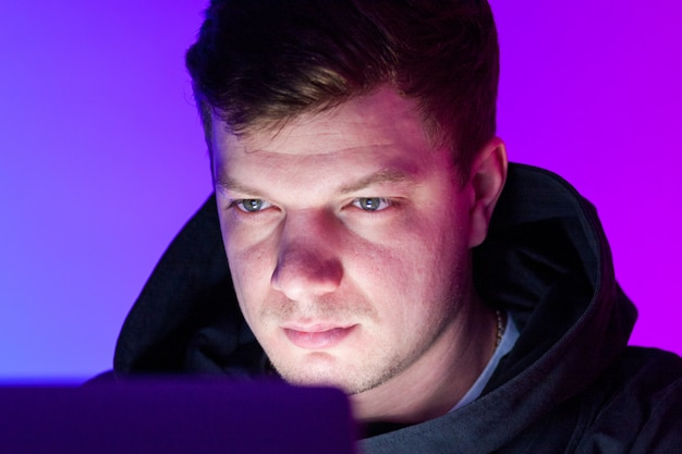 Schöner mann des nahaufnahmefotos, der am laptop arbeitet