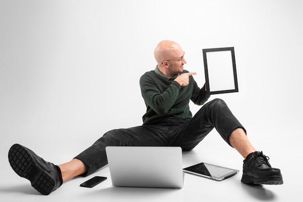 Schöner mann hält ein telefon, tablet und laptop, kommuniziert und arbeitet.