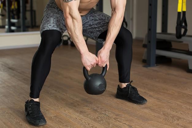 Schöner mann hockt mit kettlebell im fitnessstudio
