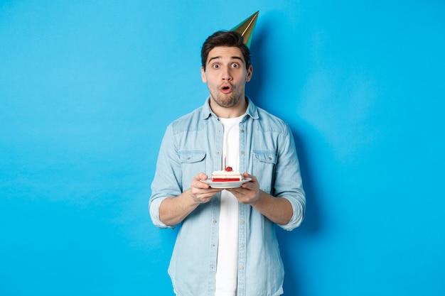 Schöner mann im partykegel, der geburtstagskuchen hält, überrascht aussieht und auf blauem hintergrund steht