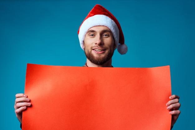 Schöner mann in einem weihnachtlichen orange mockup-plakat auf blauem hintergrund