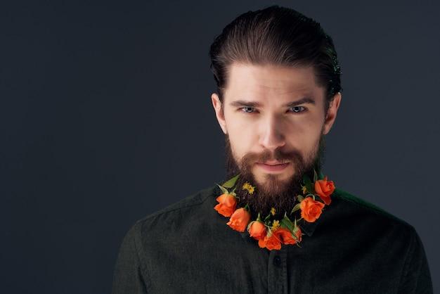 Schöner mann mit bartblumendekoration dunklem hintergrund