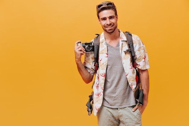 Schöner mann mit ingwerbart in weißem hemd und kariertem t-shirt lächelt und hält kamera an isolierter orangefarbener wand