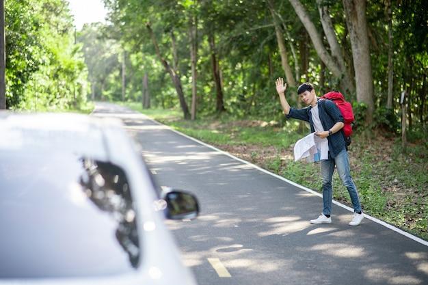 Schöner mann mit rucksack und papierkarte in der hand, er hebt die hand, um ein auto am straßenrand zu trampen, trampkonzept