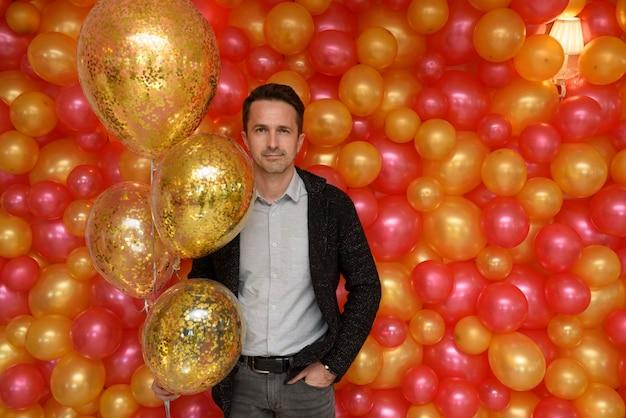 Schöner mann posiert mit goldenen kugeln auf der hintergrundwand von fotos von roten und gelben ballons