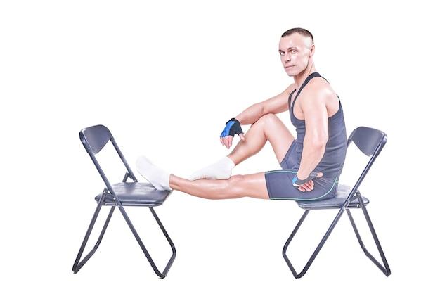 Schöner mann sitzt in sportkleidung auf den stühlen isoliert auf weißem hintergrund