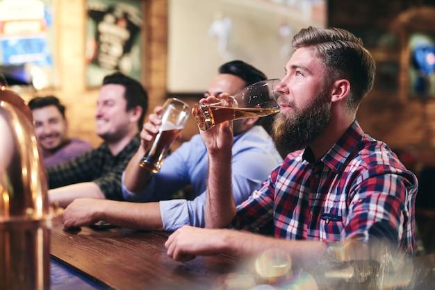 Schöner mann trinkt bier an der bar