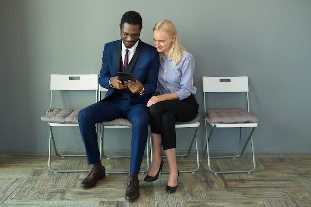 Schöner mann und frau im büro auf stühlen