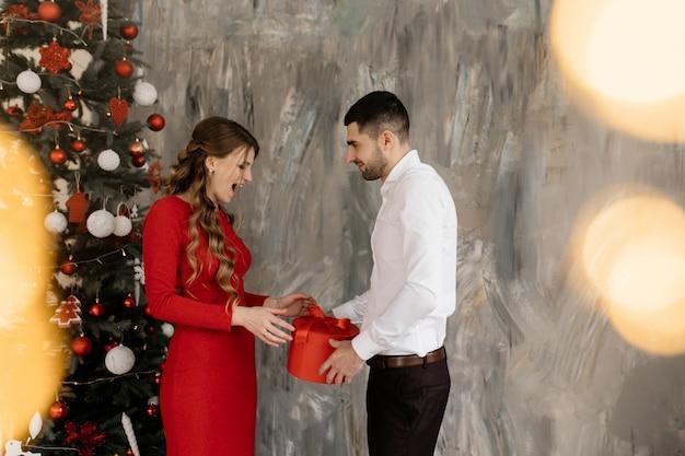Schöner mann und frau in der phantasie schließt vor reich verziertem weihnachtsbaum und tauschen ihren aus