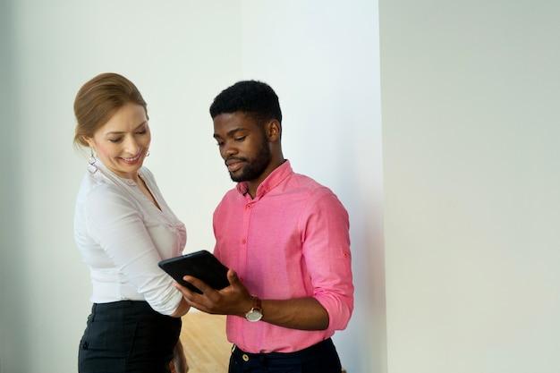 Schöner mann und frau mit tablette im büro