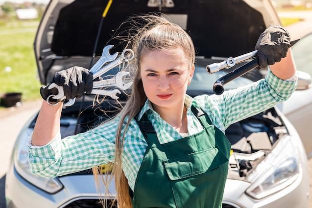 Schöner mechaniker, der mit verschiedenen werkzeugen vor dem auto aufwirft