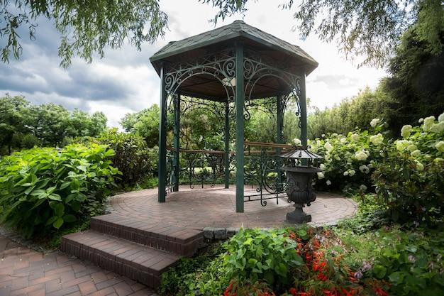 Schöner metallpavillon unter großem alten baum im park