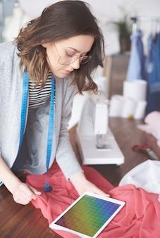 Schöner modedesigner, der auf dem pc-tablet surft