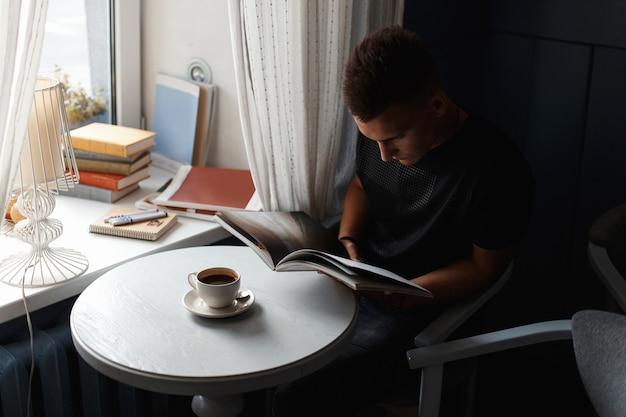 Schöner moderner mann ruht sich in einem restaurant aus, liest ein buch und trinkt kaffee.