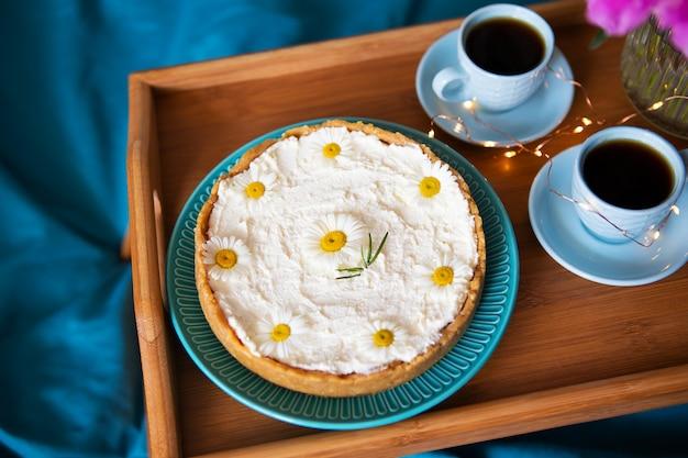Schöner morgen vanille-käsekuchen, kaffee, blaue tassen, rosa pfingstrosen in einer glasvase.