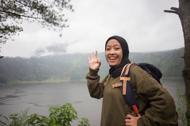 Schöner muslimischer asiatischer frauenwanderer, der erstaunliche landschaften nahe wildem bergsee genießt