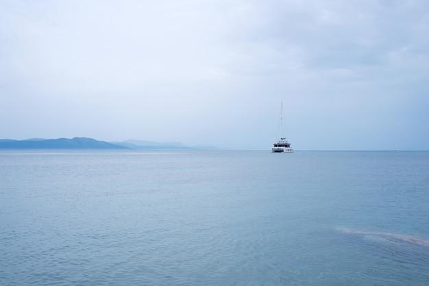 Schöner mysteriöser naturhintergrund mit yacht auf dem ozean gegen die nebelhaften berge
