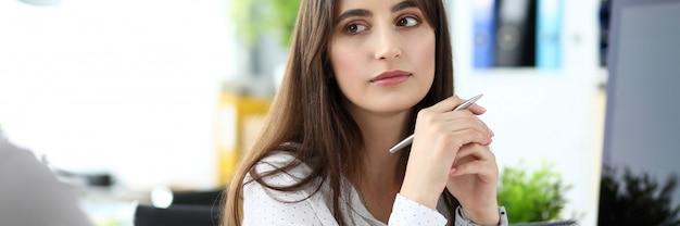 Schöner nachdenklicher weiblicher angestellter, der gegner, büroarbeitsplatz hört