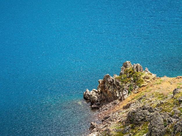 Schöner naturhintergrund des steinigen bodens im türkisfarbenen transparenten wasser des gletschersees im sonnenlicht. sonnige kulisse mit vielen steinen im grünen klaren wasser des gletschersees.