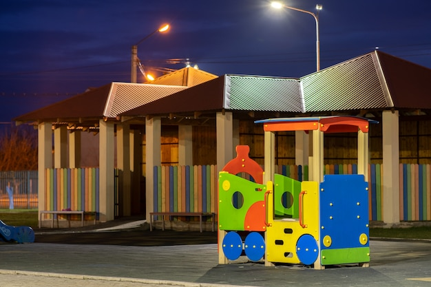 Schöner neuer moderner spielplatz im kindergarten mit weichem gummiboden und hellem neuen mehrfarbigem großen spielzeugauto