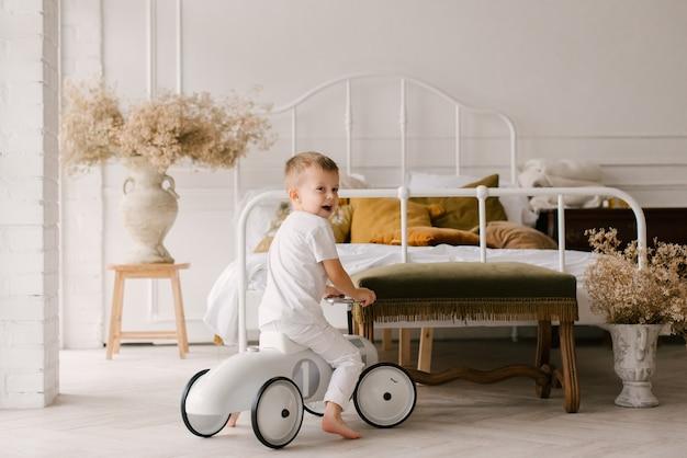 Schöner niedlicher vierjähriger junge in weißen kleidern reitet eine schreibmaschine auf einem hellen hintergrund des hauses