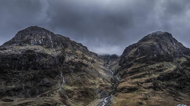 Schöner niedriger winkelschuss von felsigen hohen bergen unter einem grauen stürmischen himmel am tag
