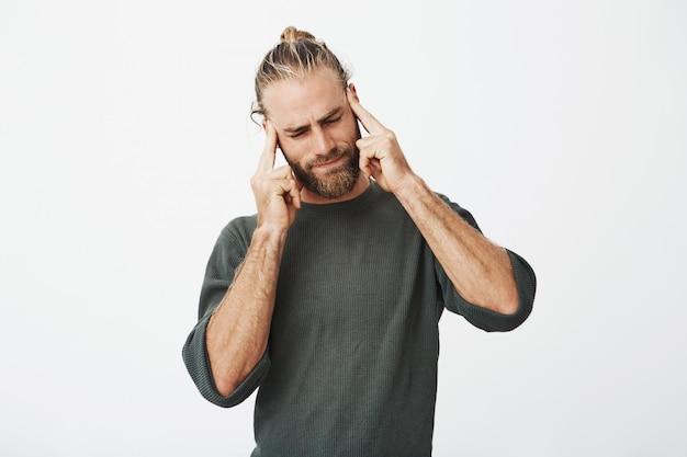 Schöner nordischer mann mit trendigem haarschnitt und bart, der müde ist und schläfen mit den fingern massiert, die versuchen, sich zu konzentrieren