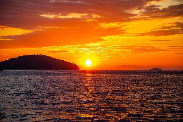 Schöner orangefarbener sonnenuntergang über meerwasser in kroatien
