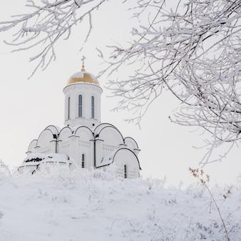 Schöner orthodoxer weißer tempel unter schneebedeckten bäumen