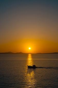 Schöner ozean mit einem kleinen boot, das auf wasser bei sonnenuntergang schwimmt