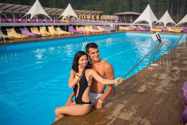 Schöner paarmann und -frau, die am rand des swimmingpools am luxuriösen erholungsort sitzt