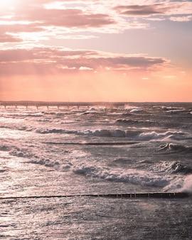 Schöner pastellfarbener sonnenuntergang mit blick auf den pier und die meereswellen