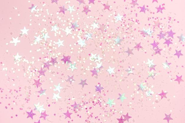 Schöner pastellrosa weihnachtshintergrund mit sternförmigen konfetti. draufsicht