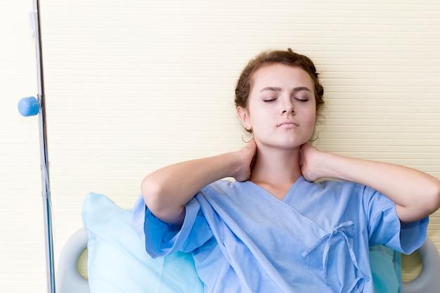 Schöner patient der jungen frau mit nackenschmerzen auf krankenhausbettraum