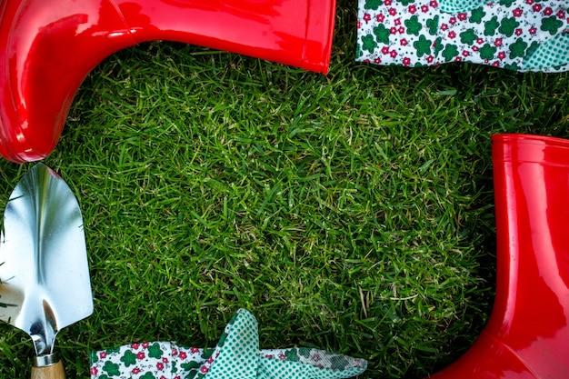 Schöner rahmen aus gartengeräten, die auf frischem grünem gras liegen