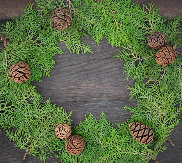 Schöner rahmen aus thuja-zweigen des weihnachtsbaumes und der zapfen. weihnachtskranz auf dunklem holzbrett. speicherplatz kopieren Premium Fotos