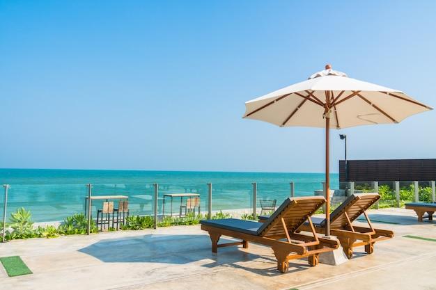 Schöner regenschirm und stuhl rund um den pool in hotel und resort