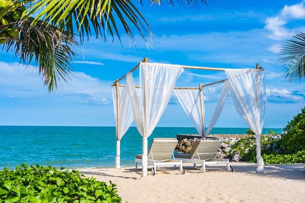 Schöner regenschirm und stuhl um strandseeozean mit blauem himmel für reise