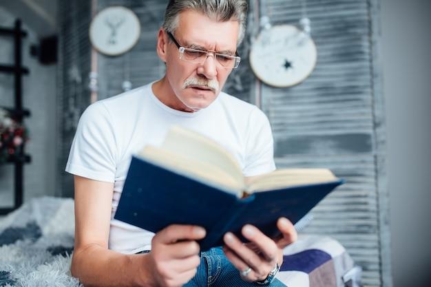 Schöner reifer mann liest ein buch auf dem sofa in seinem wohnzimmer