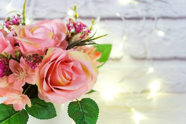 Schöner romantischer blumenstrauß der rosa rosen auf weißem backsteinmauerhintergrund mit leuchtenden lichtern und raum für text. valentinstag, hochzeitskonzept.