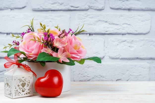 Schöner romantischer blumenstrauß der rosa rosen mit roter herzform und durchbrochener geschenkbox auf weißem backsteinmauerhintergrund. valentinstag, hochzeitskonzept.
