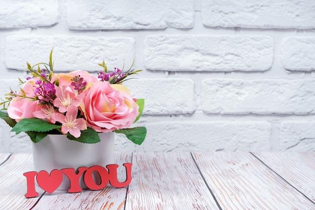 Schöner romantischer blumenstrauß von rosa rosen mit hölzernem rosa zeichen ich liebe dich auf weißem backsteinmauerhintergrund. valentinstag, hochzeitskonzept.