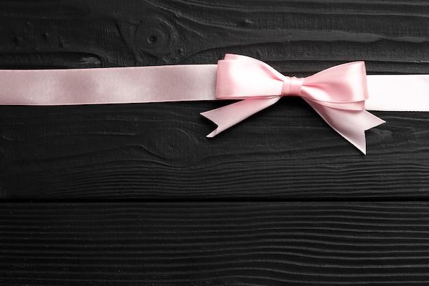 Schöner rosa bogen und band auf schwarzem hölzernem hintergrund. herzlichen glückwunsch konzept.